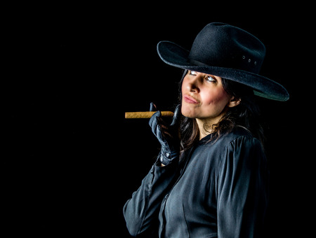 Brunette woman in black dress, black gloves, and wearing a black cowboy hat standing in front of a black backdrop, holding a cigar between her fingers and looking upwards with a playful expression on her face. Stock fotó