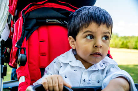 look latino: Close up shot of latino child sitting in a red stroller outside and looking off to the side Stock Photo