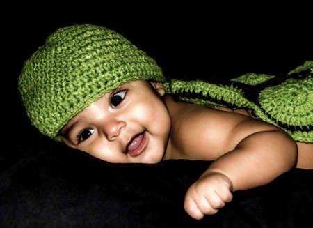 smiing: Close up shot of a smiing latino baby laying on a black cushion with a black background and wearing a green cap.