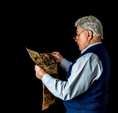 oude krant: Low key shot van de oudere man in de voorkant van een zwarte achtergrond draagt een trui vest en een bril en het lezen van een oude krant.