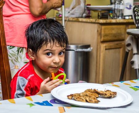 look latino: Latino child sitting at a table with food on a plate in front of him, holding a sippy cup and looking at the camera with a mischievous look on his face