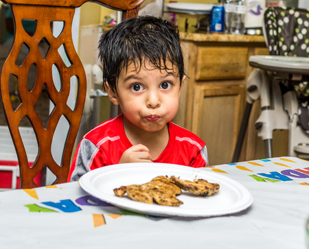 Latino child sitting at a table with food on a plate in front of him and looking at the camera with a funny look on his face