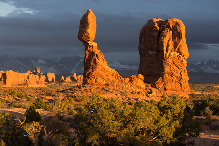Balanced Rock in the late afternoon light with distant Arches and Monoliths lit against a stormy backdrop. Stock Photo