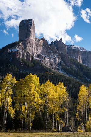 Chimney Rock  and Court House Mountain stands above an aspen grove along Owl Creek Pass road.