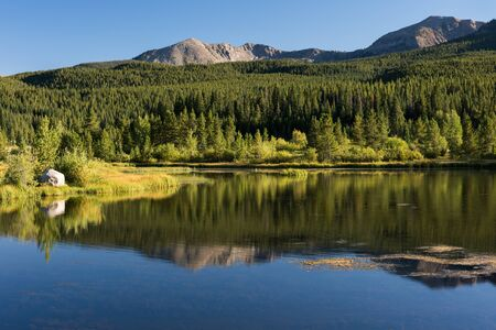 Early autumn reflection of mountain range within White River National Forest in Central Colorado. Standard-Bild