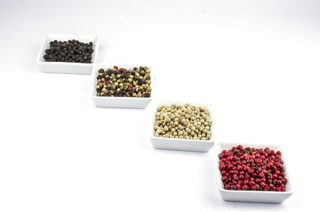 sorted: Red, white, black and sorted peppercorns on white Stock Photo