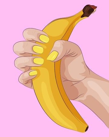 Plátano en mano de mujer con uñas amarillas. Foto de archivo - 75250657