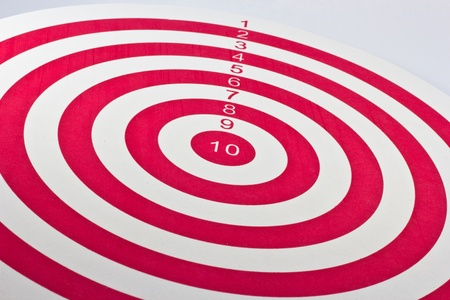 Red target dart board with darts on white background photo