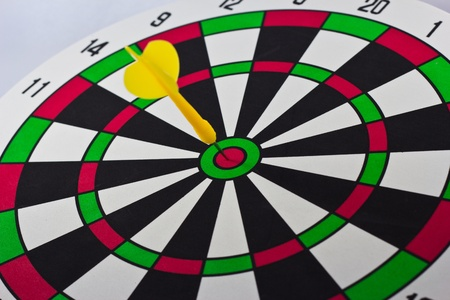 taget: Colorful darts at a target. Red dart hit the aim.