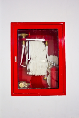 Fire hose in the box hanging on the wall photo