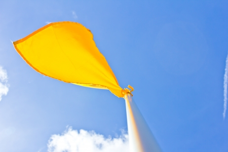 yellow flag at field on blue sky background photo