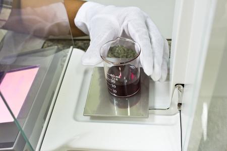 balanza de laboratorio: Sustancia de ensayo en el laboratorio - cubilete con productos qu�micos en la balanza electr�nica. Foto de archivo