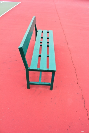 sidelit: green chair in the tennis court.