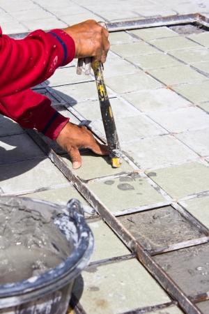 Ttiles floor installation.Worker installs ceramic tile photo