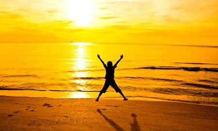 Silhouette of a young boy jumping on the beach photo