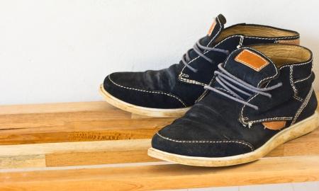 modelos negras: Un par de zapatillas de lona negros en los estantes de madera
