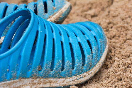 Blue flip flops laying on the sandy  photo