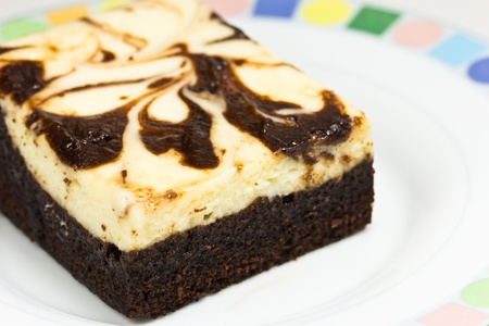 Frosted chocolate cheese brownie on white background   Macro with extremely shallow dof  photo