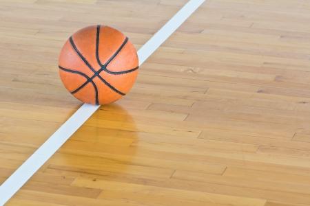 cerrar: Baloncesto balón sobre el piso en el gimnasio