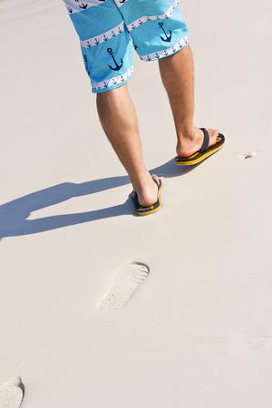 A man walking on sand beach photo