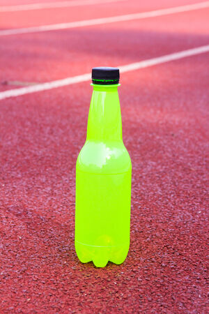 green bottle  water on running track photo