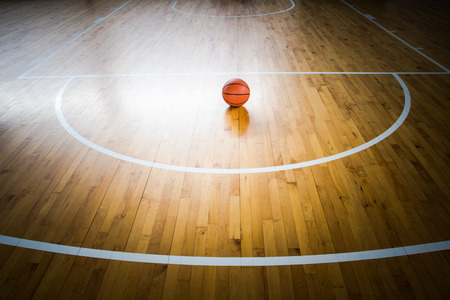 balle de basket-ball sur un plancher dans la salle de gym