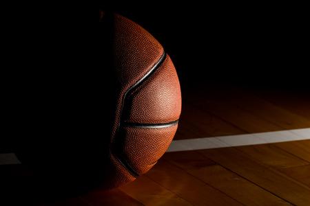 baloncesto: Baloncesto aislado en la corte fondo negro con efecto de luz