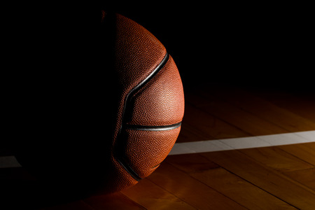 Basketball isolated on court black background with light effect photo