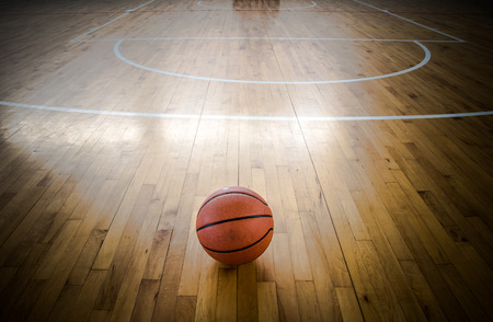 terrain de basket: balle de basket-ball sur un plancher dans la salle de gym