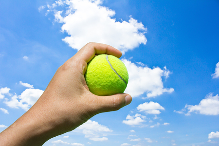 Hand holding tennis ball on blue sky background photo