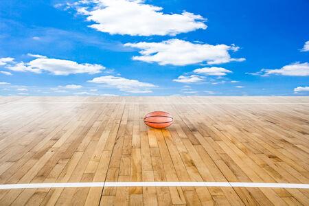 Basketball ball over floor with blue sky photo