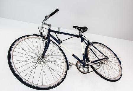 fixed: bicicleta fija del engranaje en la pared blanca Foto de archivo