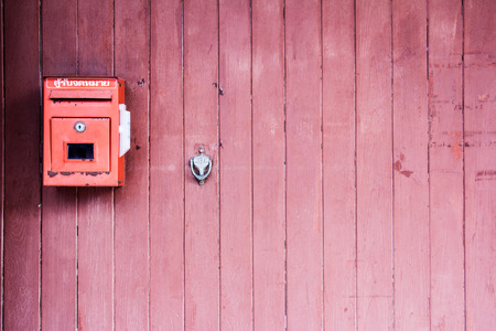 Red mailbox on the red wooden door photo