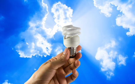 electric bulb: Electric bulb in hand on blue sky background