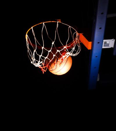 光の効果と黒の背景にバスケット ボール フープ 写真素材