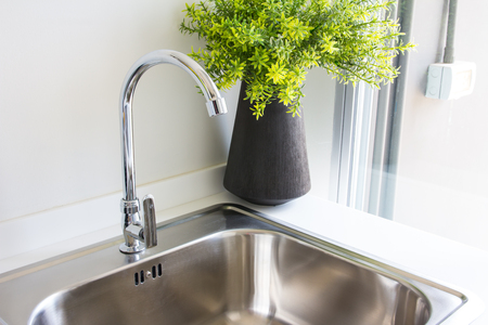 cold steel: Water tap with sink in  modern kitchen.