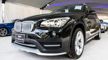 front views: HATYAI, THAILAND - AUGUST 12, 2015: New model BMW X1 sDrive18i against modern design .