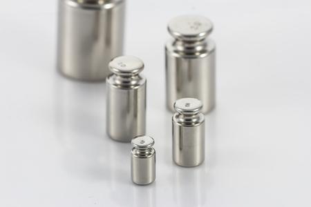 balanza de laboratorio: Pesa de calibración en el fondo blanco