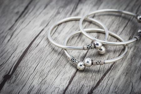 Silver bracelet on wooden background Standard-Bild