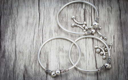 silver background: Silver bracelet on wooden background Stock Photo
