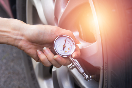 Checking car tyre pressure with gauge