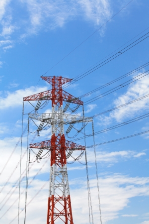 powerline: High voltage powerline and pylon against bright blue sky with white clouds