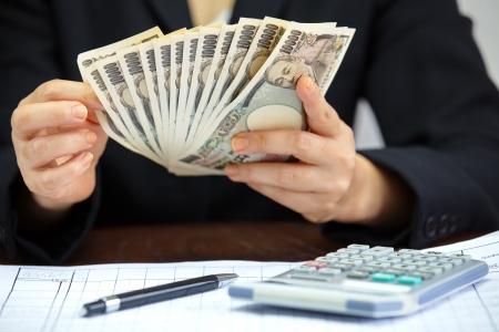 手のお金、日本の通貨のノート、日本円を数える