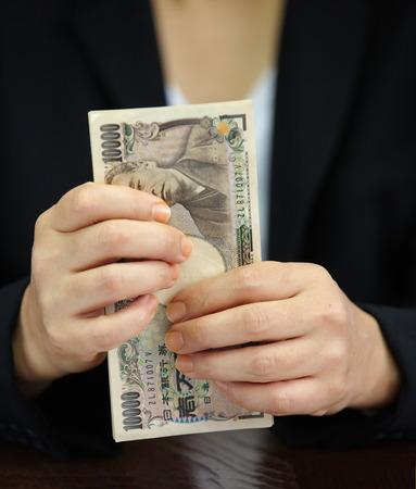 contando dinero: Mano que cuenta el dinero, nota de la moneda japonesa, el yen japon�s Foto de archivo