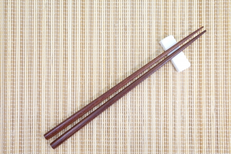 brown wood chopsticks and traditional bamboo plate mat  photo