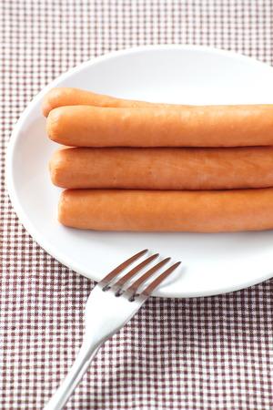 wienie: Raw frankfurter sausage with dish and fork
