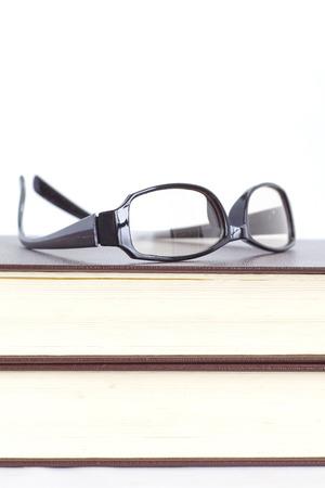 白い背景の上の眼鏡と読書の本