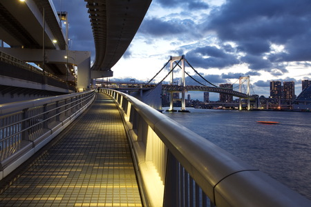 Tokyo bay and rainbow bridge at sunset time from  walking across photo