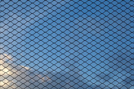 Metal wire mesh and evening blue sky in background Stock Photo