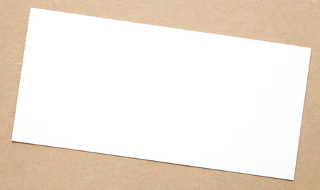 brown paper background: Blank white paper note on brown paper background
